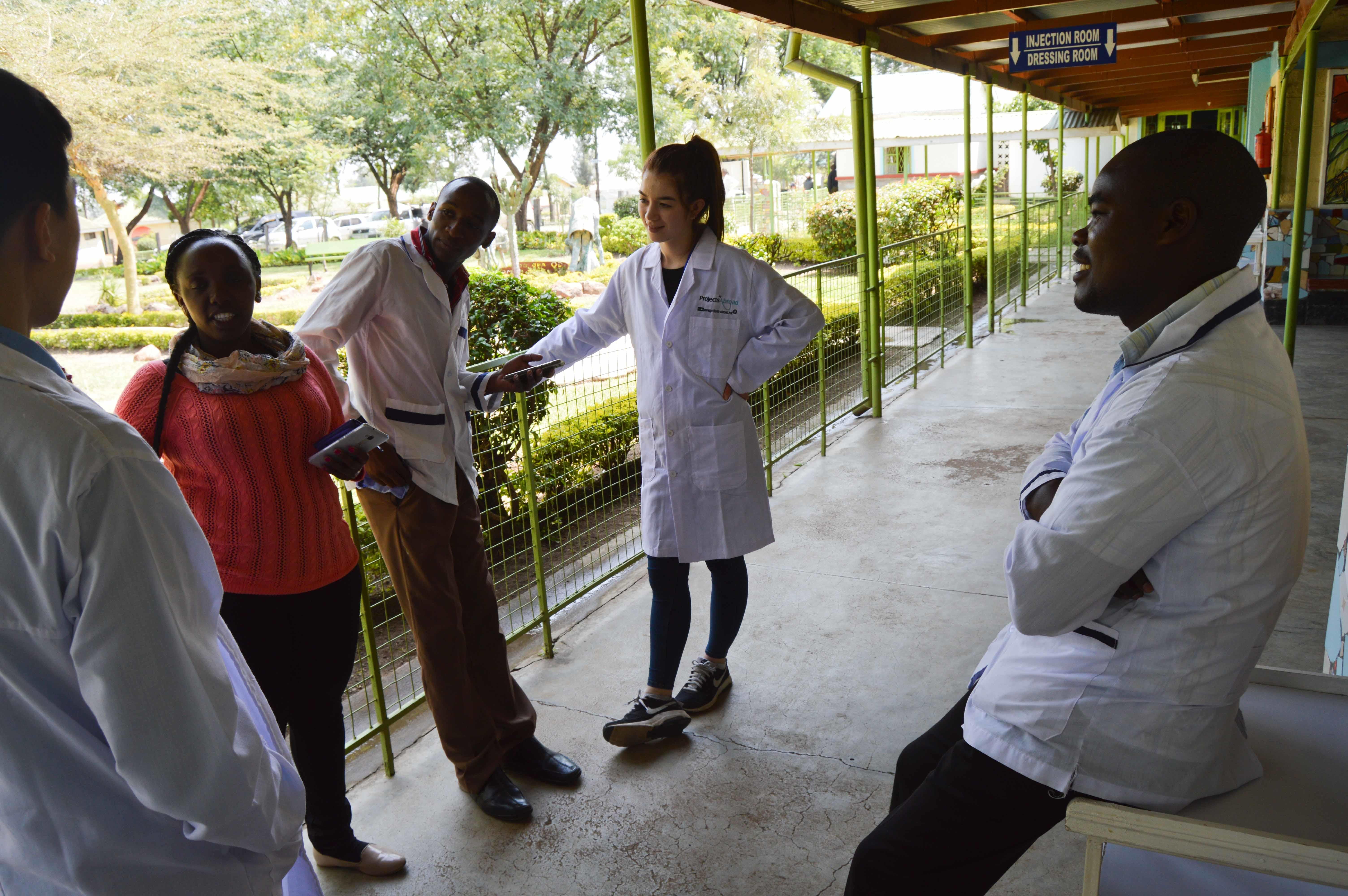 Projects Abroad occupational therapy in Kenya interns are pictured conversing with local doctors outside the hospital during their work experience.
